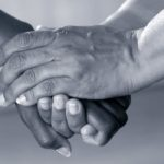 fotografia en blanco y negro de tres manos entrelazadas simbolizando la bondad
