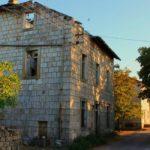 imagen de una casa en ruinas de dos pisos caminos de tierra y algunos arboles