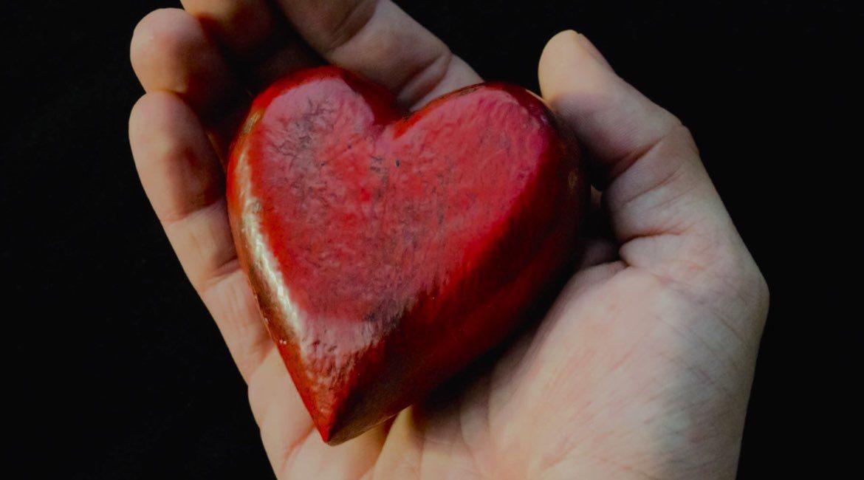 una mano sosteniendo un corazon rojo sabes de que lado esta el corazon