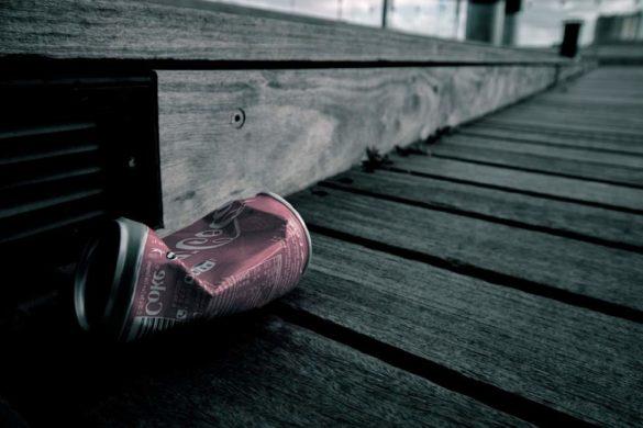 lata de refresco de cola color roja tirada en la calle al frente de una coladera