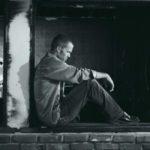 joven sentado recargado en un muro con cara triste ya que dormir mal causa depresion