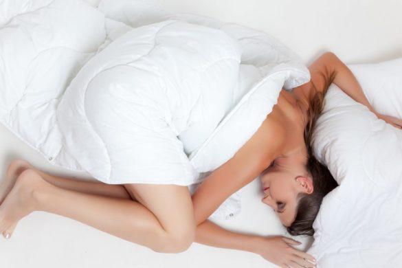 mujer acostado envuelta en sabanas desnuda los beneficios para la salud al dormir desnudos