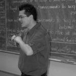 hombre de camisa y lentes frente a un pizarron conoce los beneficios de aprender un idioma