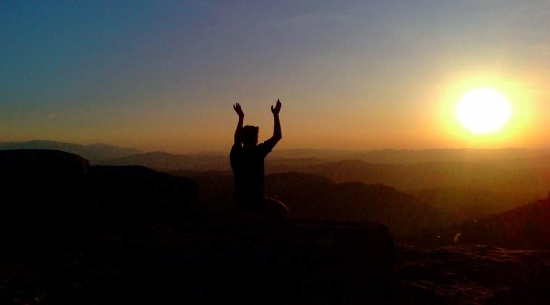 persona sentada en la cima viendo el ocaso con las manos levantadas pensamientos positivos