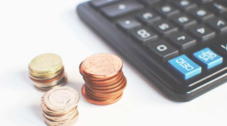 parte de calculadora negra con tres torres de monedas de diferentes denominaciones