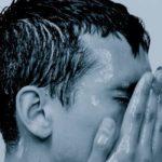 hombre bajo la ducha con sus manos en la cara las cosas que no sabias del shampoo