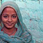 mujer indu de piel moren con velo color azul turquesa y pared de tabique azul de fondo