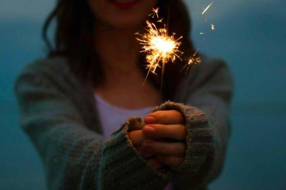 mujer de sueter gris sosteniendo una luz descubriendo el secreto para vivir alegre