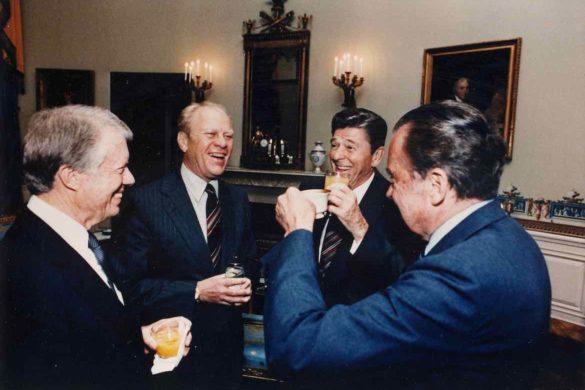 cuatro hombres mayores de traje y corbata sonriendo y tomando bebidas en diferentes vasos