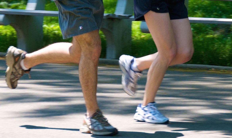 pies de dos personas corriendo en tenis y con short conoce como evitar los calambres