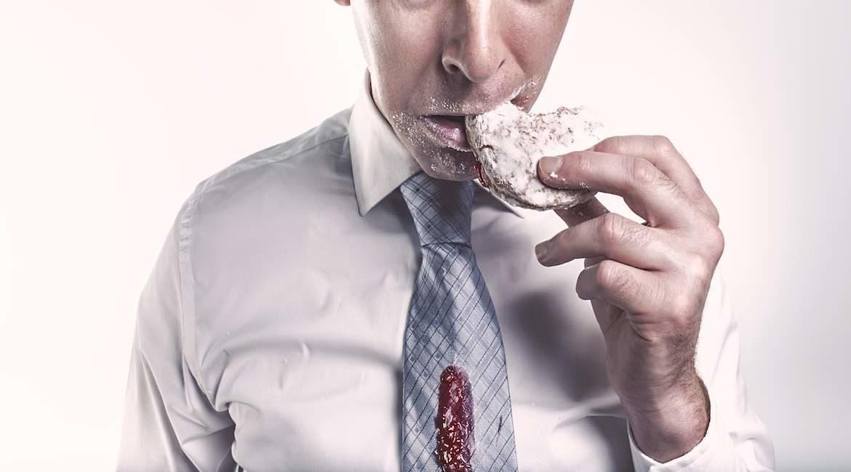 hombre de camisa y corbata azul de rombos manchada con jalea comiendo un pan glaseado