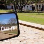 calle y banqueta empedrada casas y espejo retrovisor de un auto con el reflejo de una casa