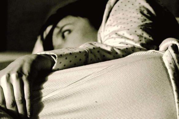 mujer en pijama recostada sin poder dormir y propensa a desarrollar enfermedades