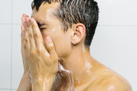 joven desnudo con cabello y cuerpo mojado y con sus manos sobre su cara
