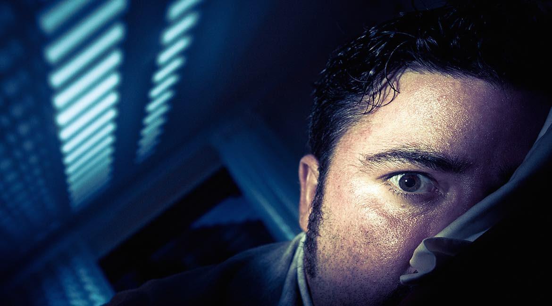 hombre en habitacion oscura con ojo abierto la razon por la que te despiertas a media noche