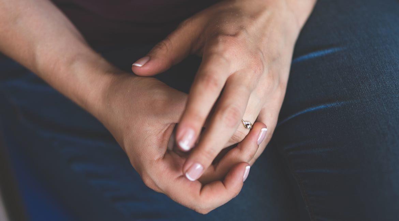 par de manos de mujer con la punta de las unas pintadas de blanco y anillo en dedo anular