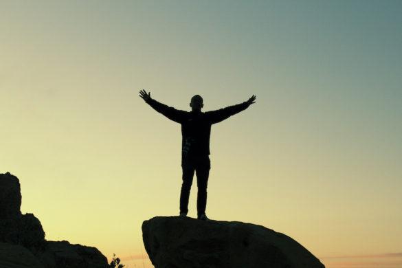 hombre en la cima de una roca con las manos levantadas de fondo el cielo entre y mas rocas