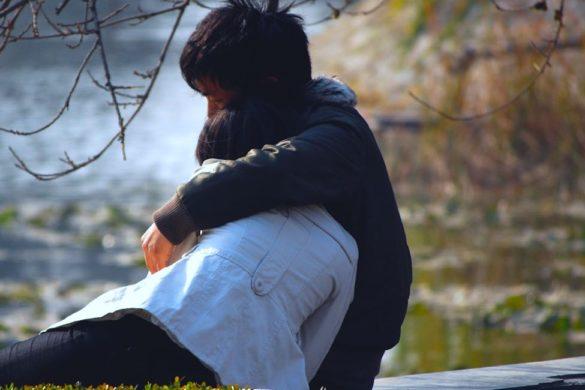 hombre y mujer sentados abrazados en un parque de fondo agua y maleza de platas y arboles