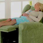mujer mayor dormida en un sofa reclinable color verde dentro de una casa