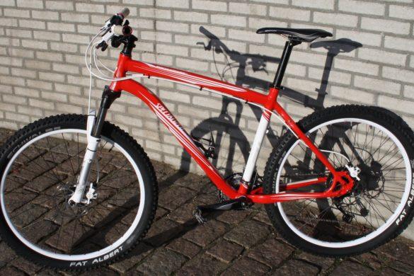 foto de una bicicleta color roja y blanca recargada en la pared de tabiques color gris