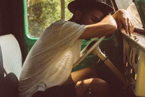 hombre con sombrero y playera blanca dentro de un auto recargado sobre volante