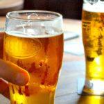 mano con vaso de cerveza clara junto a otro vaso de cerveza beneficios de tomar cerveza diario