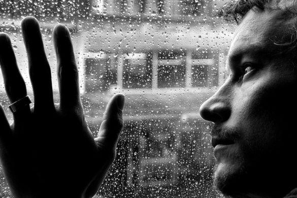 hombre con la mano en la ventana con mirad triste una las cinco senales de infelicidad