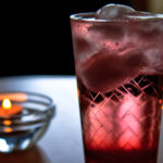 vela y vaso con bebida color rojo y hielos sabes que son los trastornos hidroelectricos