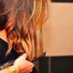 mujer pasando plancha de cabello por su cabeza descubre como no despeinarse al dormir