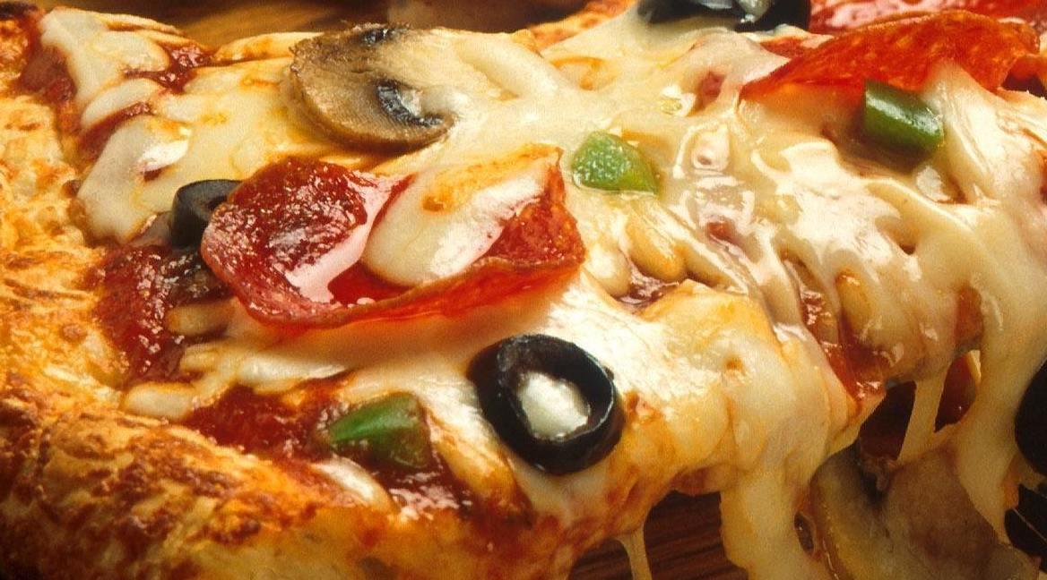 rebanada de pizza con queso aceitunas champinones alimentos que provocan hipertension