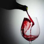 botella de vino color rojo sirviendo en una copa de cristal el vino mejora la memoria