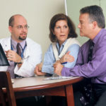 doctor con radiografia y dos pacientes explicando sobre fracturas en adultos mayores