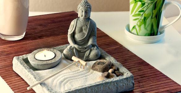 mesa con vaso de leche una taza mantel color cafe y escultura de buda con arena y rocas