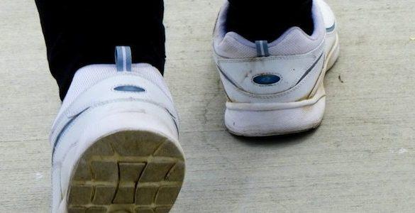 par de pies con pantalon negro y tenis blancos mostrando como adelgazar caminando