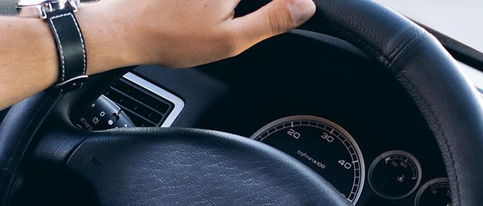 fotogafia de bolante y parte del tablero de un auto color negro y brazo con reloj