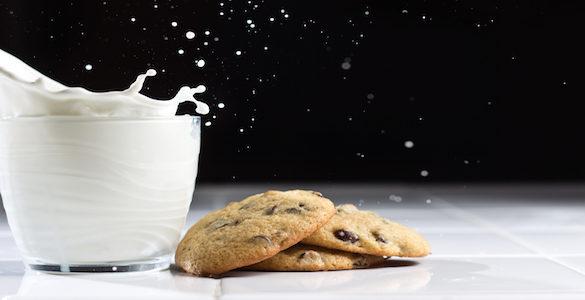 vaso de leche con galletas de chispas de chocolate que causa la intolerancia a la lactosa