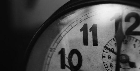 foto en blanco y negro de la parte de un reloj se observan tres numeros y una manecilla