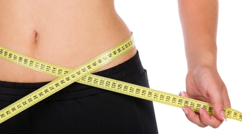 mujer midiendo su cintura con cinta metrica amarilla mira los consejos para bajar de peso