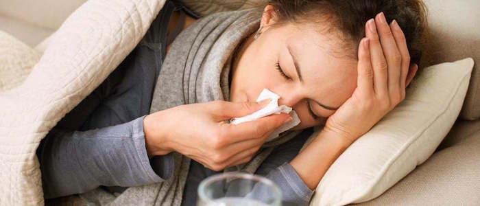 mujer acostada con bufanda y pijama gris limpiando su nariz vick vaporub es el remedio