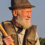 hombre de la tercera edad con chaleco camisa y sombrero sosteniendo un palo de madera