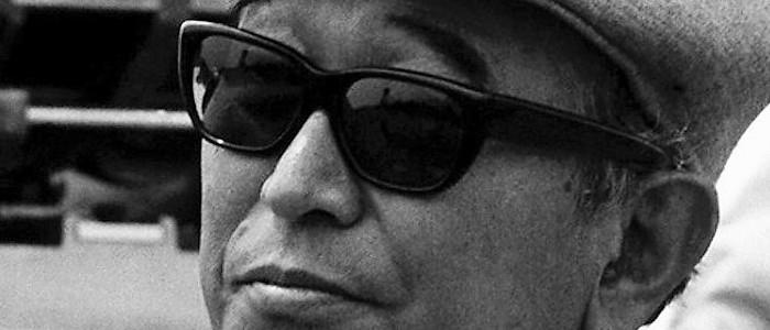 fotografia en blanco y negro del escritor akira kurosawa con lentes oscuros y boina