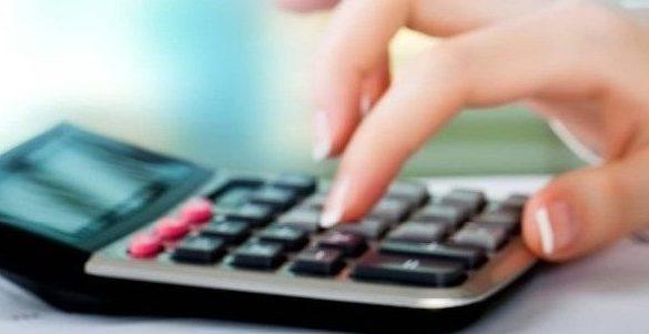 manos de mujer con la punta de las unas pintada tecleando botones de una calculadora