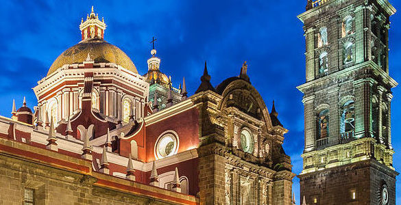 fotografia de la parte alta de una iglesia iluminada se observa el cielo y las nubes