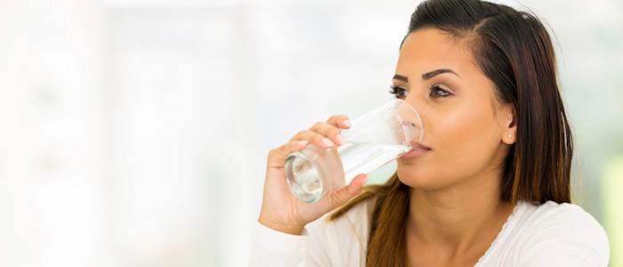 mujer de blusa blanca tomando un vaso de agua beber agua en ayunas combate enfermedades