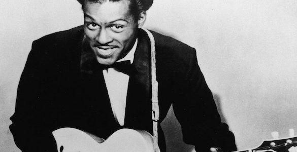 fotografia en blanco y negro del guitarrista chuck berry con traje negro mono y guitarra