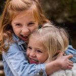 dos ninas dandose un gran abrazo en un bosque muestra del beneficio del contacto fisico