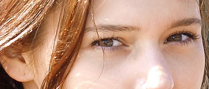 fotografia de la cara de una mujer resalta su cabello castano ojos verdes nariz y oreja