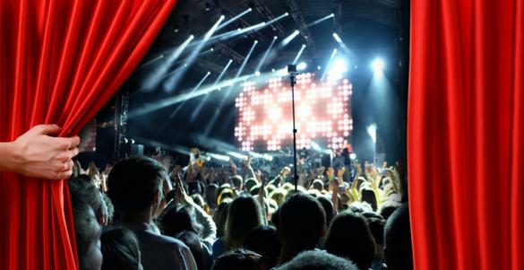mano abriendo telon rojo de un escenario de teatro con espectadores y show en vivo
