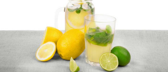 par de vasos de cristal con jugo de limon y hierbabuena tambien limones esteros y partidos
