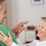par de adultos mayores sonriendo bailando el playera verde y ella con blusa blanca